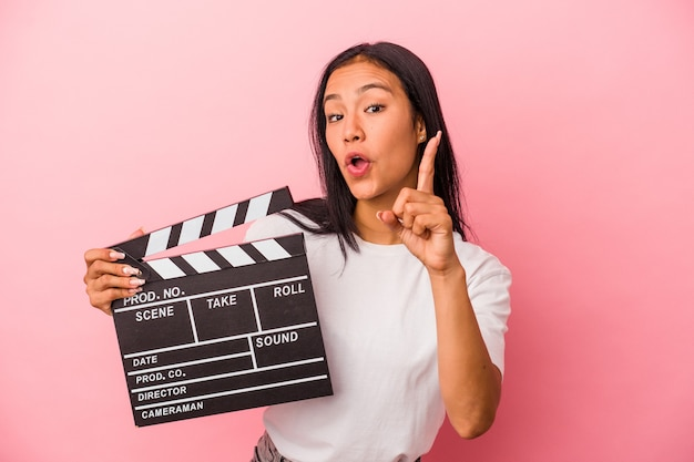 Young latin woman holding clapperboard isolated on pink background  having an idea, inspiration concept.