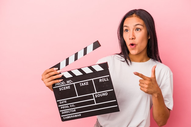 Young latin woman holding clapperboard isolated on pink background  pointing to the side