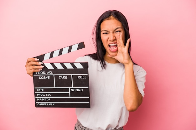 Young latin woman holding clapperboard isolated on pink background  shouting and holding palm near opened mouth.