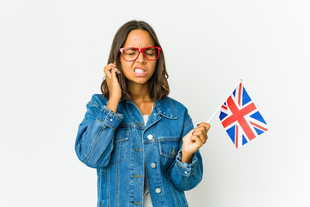 Young latin woman holding a english flag covering ears with fingers, stressed and desperate by a loudly ambient.