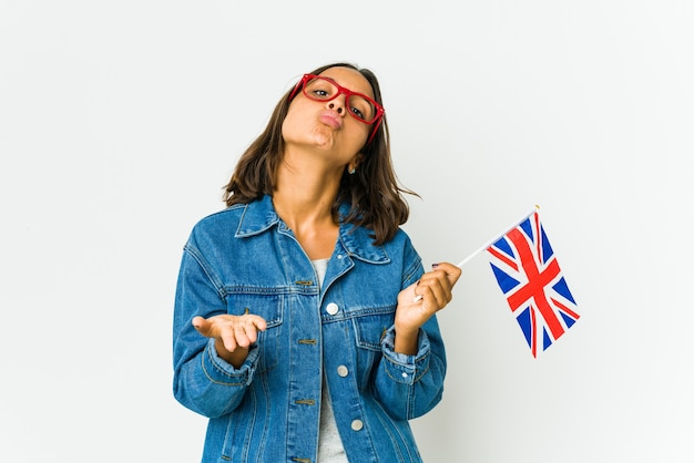 Young latin woman holding a english flag folding lips and holding palms to send air kiss.