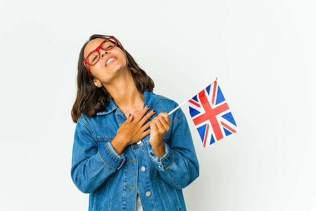 Young latin woman holding a english flag has friendly expression, pressing palm to chest. love concept.
