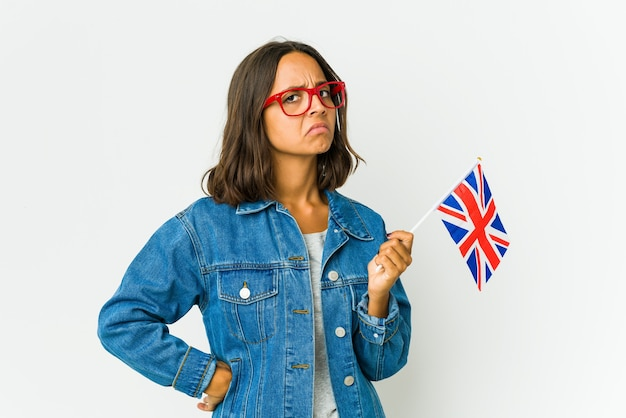 Young latin woman holding a english flag isolated on white wall frowning face in displeasure, keeps arms folded.