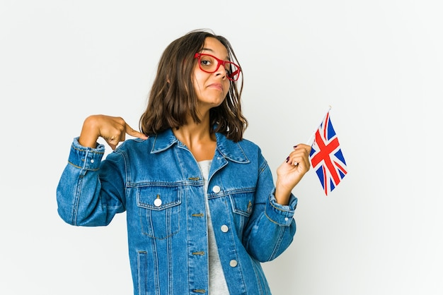 Young latin woman holding a english flag isolated on white wall person pointing by hand to a shirt copy space, proud and confident