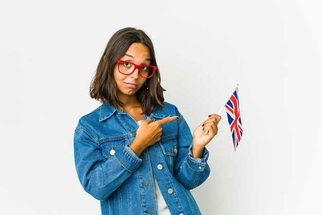 Young latin woman holding a english flag isolated on white wall pointing with forefingers to a copy space, expressing excitement and desire.