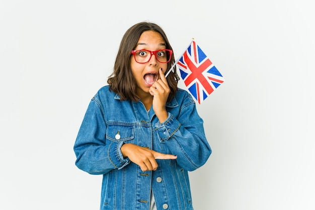 Young latin woman holding a english flag isolated on white wall saying a gossip, pointing to side reporting something.