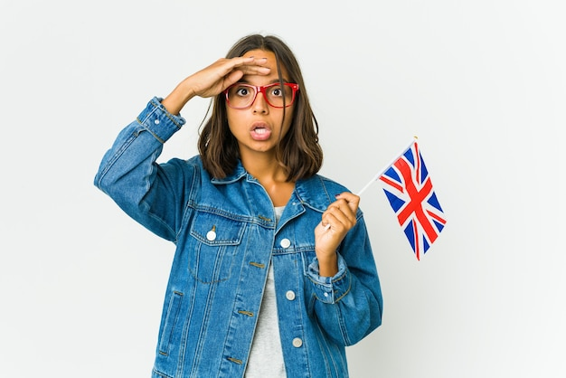 Young latin woman holding a english flag looking far away keeping hand on forehead.