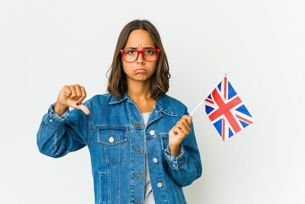 Young latin woman holding a english flag showing a dislike gesture, thumbs down. disagreement concept.