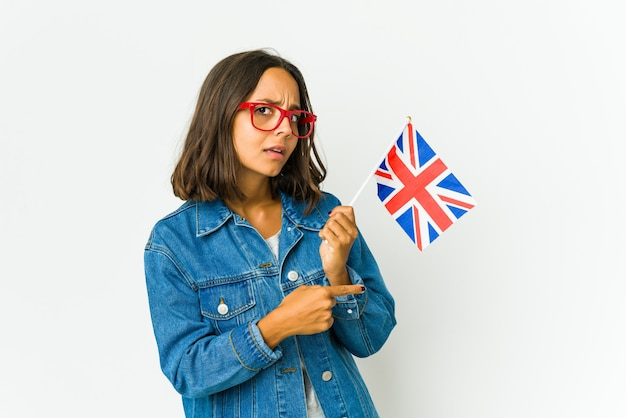 Young latin woman holding a english flag trying to listening a gossip.