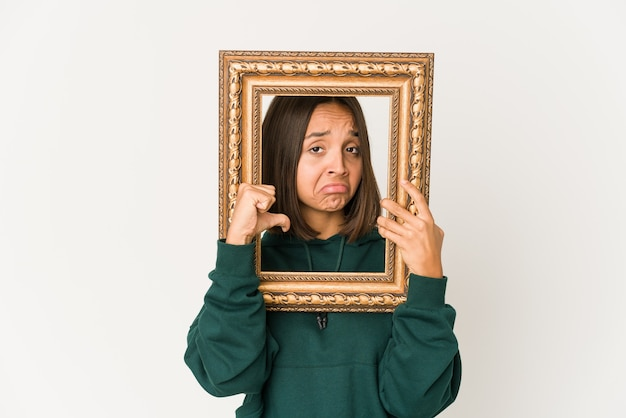 Young latin woman holding a frame