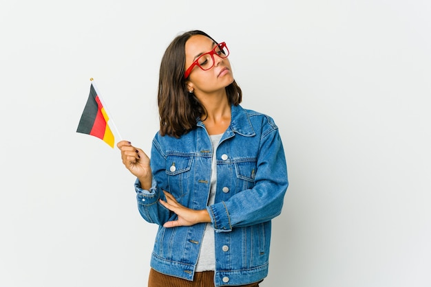 Young latin woman holding a german flag dreaming of achieving goals and purposes