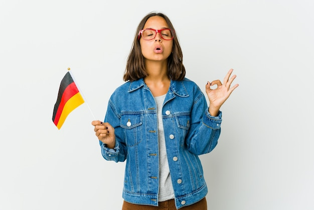 Young latin woman holding a german flag isolated on white wall relaxes after hard working day, she is performing yoga.