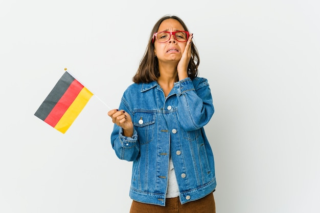 Young latin woman holding a german flag whining and crying disconsolately.