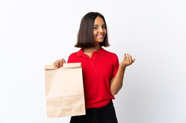 Young latin woman holding a grocery shopping bag isolated on white inviting to come with hand. happy that you came