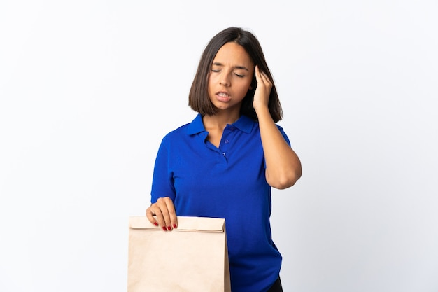 Young latin woman holding a grocery shopping bag isolated on white with headache