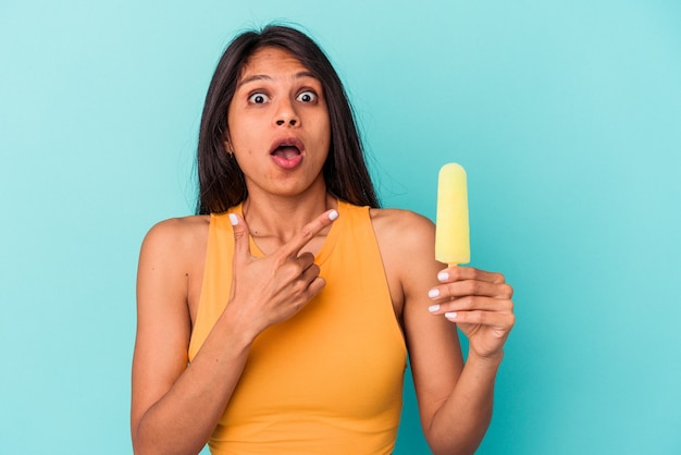 Young latin woman holding ice cream isolated on blue background pointing to the side
