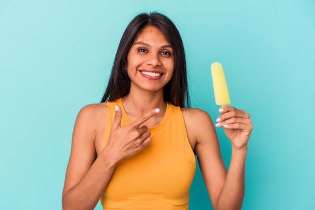 Young latin woman holding ice cream isolated on blue background smiling and pointing aside, showing something at blank space.