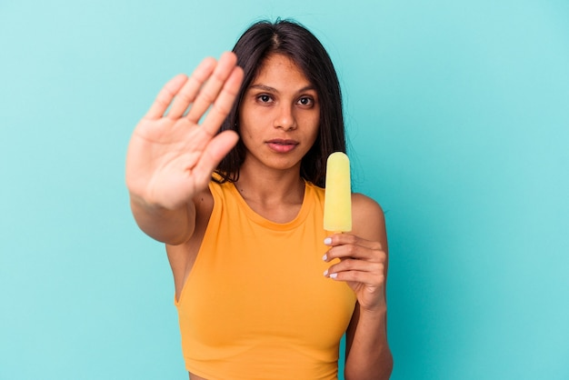 Young latin woman holding ice cream isolated on blue background standing with outstretched hand showing stop sign, preventing you.