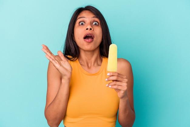 Молодая латинская женщина, держащая мороженое на синем фоне, удивлена и потрясена.