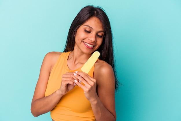 Молодая латинская женщина, держащая мороженое на синем фоне