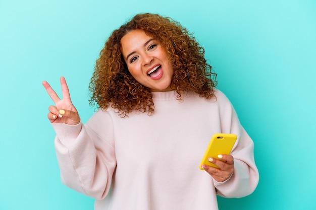 青の背景に携帯電話を保持している若いラテン女性は、うれしくて屈託のない指で平和のシンボルを示しています。