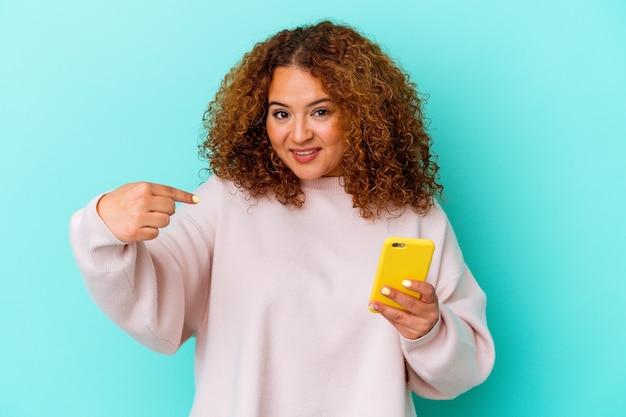 자랑스럽고 자신감이 셔츠 복사 공간을 손으로 가리키는 파란색 배경 사람에 고립 된 휴대 전화를 들고 젊은 라틴 여자
