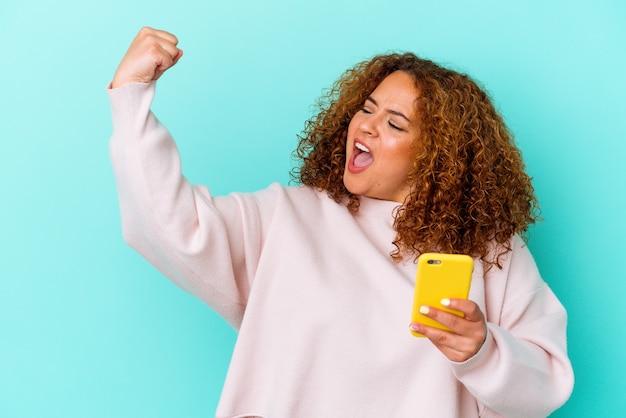 勝利、勝者の概念の後に拳を上げる青い背景に分離された携帯電話を保持している若いラテン女性。
