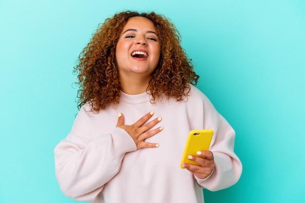 파란색 벽에 고립 된 휴대 전화를 들고 젊은 라틴 여자 큰 소리로 가슴에 손을 유지 웃음