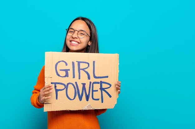 Young latin woman holding placard with text girl power