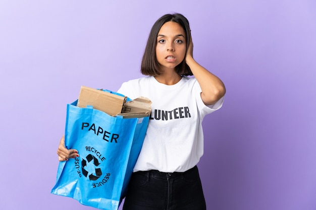 Young latin woman holding a recycling bag full of paper to recycle isolated on purple frustrated and coning ears
