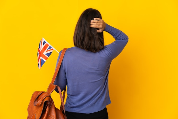 Young latin woman holding an united kingdom flag isolated on yellow background in back position and thinking