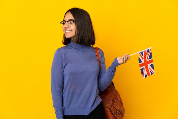 Young latin woman holding an united kingdom flag isolated on yellow background looking to the side and smiling