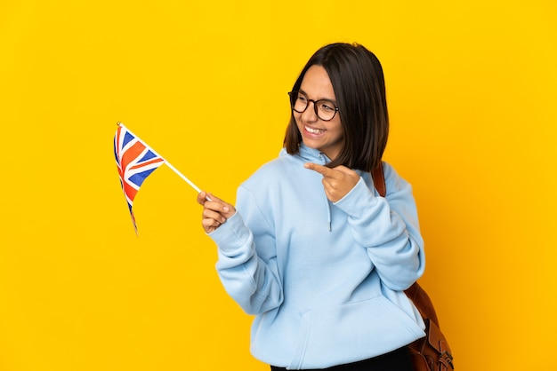 Young latin woman holding an united kingdom flag isolated on yellow background pointing finger to the side and presenting a product
