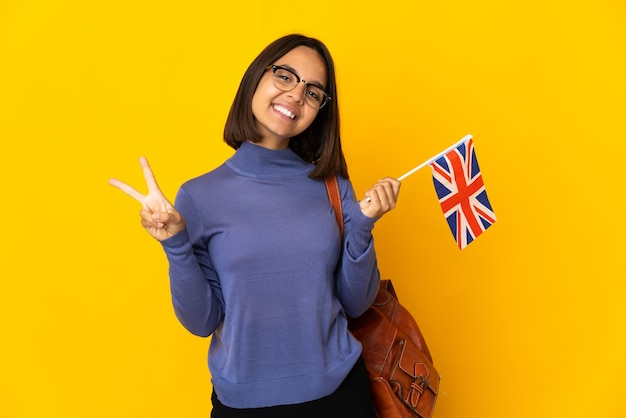 Young latin woman holding an united kingdom flag isolated on yellow background showing victory sign with both hands