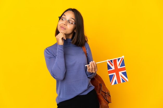 Young latin woman holding an united kingdom flag isolated on yellow background thinking an idea while looking up