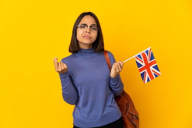 Young latin woman holding an united kingdom flag isolated on yellow wall making money gesture but is ruined