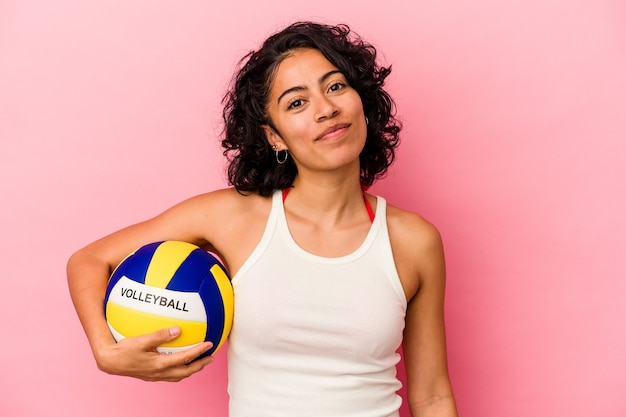 Young latin woman holding a volley ball isolated on pink background