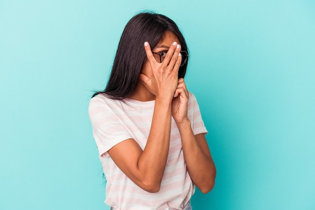 Young latin woman isolated on blue background blink through fingers frightened and nervous.