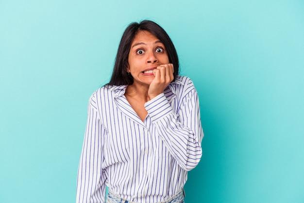 파란색 배경에 격리된 젊은 라틴 여성은 손톱을 물어뜯고 긴장하고 매우 불안해합니다.