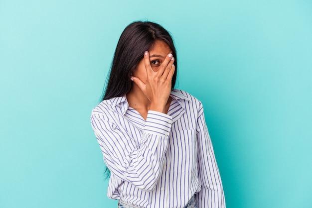 青い背景で隔離された若いラテン女性は、恥ずかしい顔を覆って、指を介してカメラで点滅します。