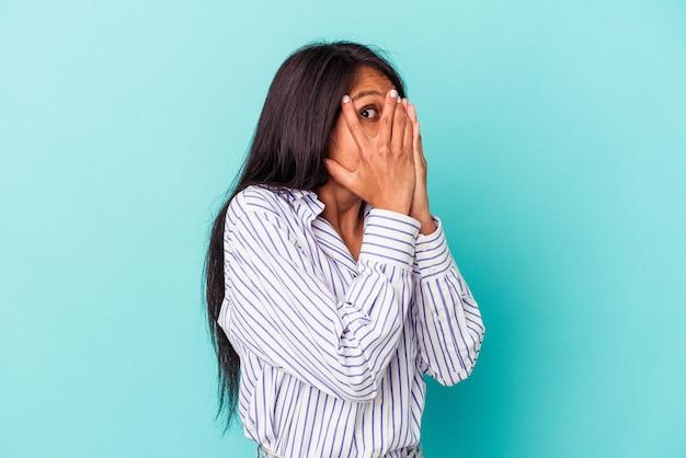 青い背景で隔離された若いラテン女性は、おびえ、神経質な指を点滅します。