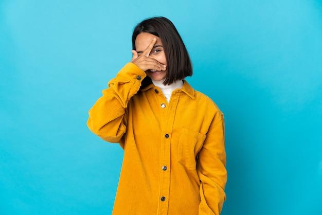 Молодая латинская женщина изолирована на синем фоне, закрывая глаза руками и улыбаясь