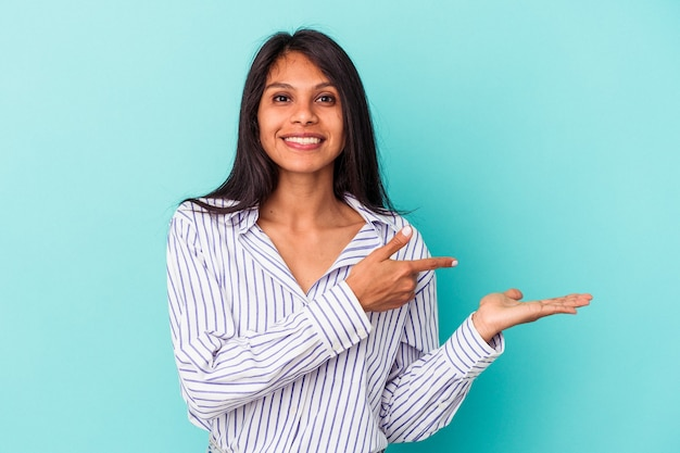 青い背景に分離された若いラテン女性は、手のひらにコピースペースを保持して興奮しました。