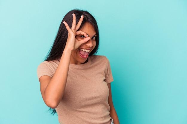 青い背景に孤立した若いラテン女性は、目に大丈夫なジェスチャーを維持して興奮しました。