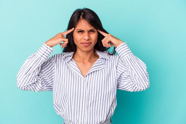 Молодая латинская женщина, изолированная на синем фоне, сосредоточилась на задаче, держа указательные пальцы, указывая головой.