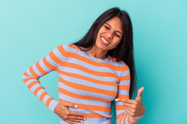 肝臓の痛み、胃の痛みを持っている青い背景で隔離の若いラテン女性。