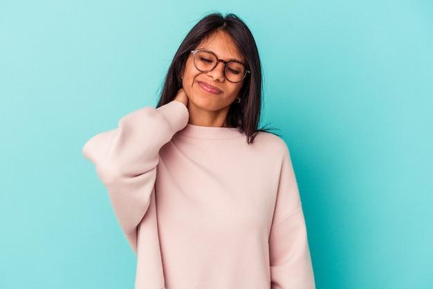ストレス、マッサージ、手で首の痛みのために首の痛みを持っている青い背景で隔離の若いラテン女性。