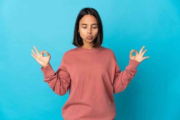 Молодая латинская женщина изолирована на синем фоне в позе дзен