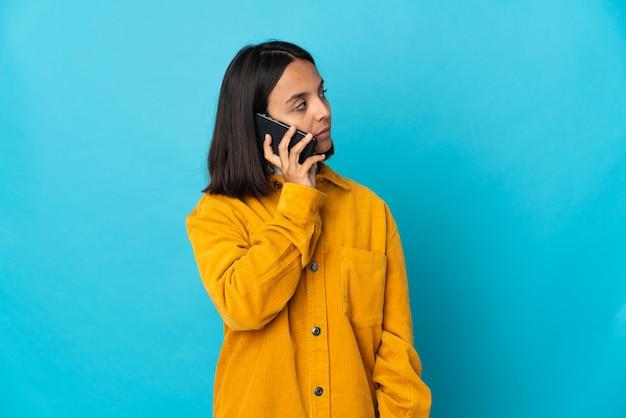 Молодая латинская женщина изолирована на синем фоне, разговаривая с кем-то по мобильному телефону
