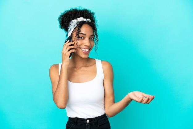 誰かと携帯電話との会話を維持している青い背景で隔離の若いラテン女性